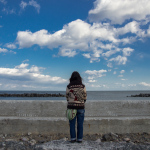 """Hisanohama"", Iwaki, Fukushima, March 11, 2014: Memorial vigils are held everywhere on the third anniversary of the Great East Japan Earthquake. At the vigil, a woman is staring at the ocean, her eyes fixed on the dark water at the horizon."