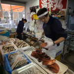 """Royal Fish Shop"", Minami Sanriku, Miyagi, October 28, 2014: At the Royal Fish Shop – located alongside 31 other stores in the Minami Sanriku Shopping Center– the owner, Youkou Endo (41), prepares to sell mizudako and madako, a special kind of octopus which is a local favorite. Sales are picking up here because many tourists visit and support these small businesses.  ""Business is booming,"" he says, ""better than before the tsunami and earthquake."""