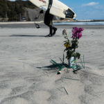 """Toyoma Beach"", Iwaki, Fukushima, March 11, 2014: On the third anniversary of the Great East Japan Earthquake, flowers and incense sticks for the deceased are placed on the beach. A cold wind blows up the fine sand in the air."